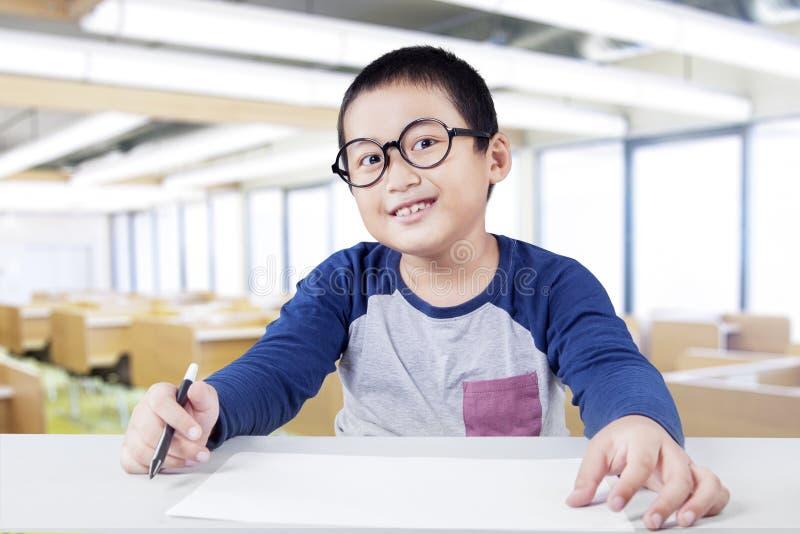 Netter kleiner Junge, der in der Klasse lächelt stockfotografie
