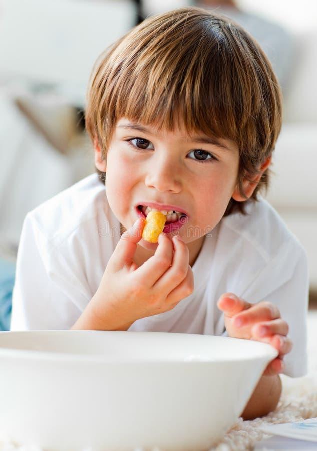 Netter kleiner Junge, der die Chips liegen auf dem Fußboden isst lizenzfreie stockbilder