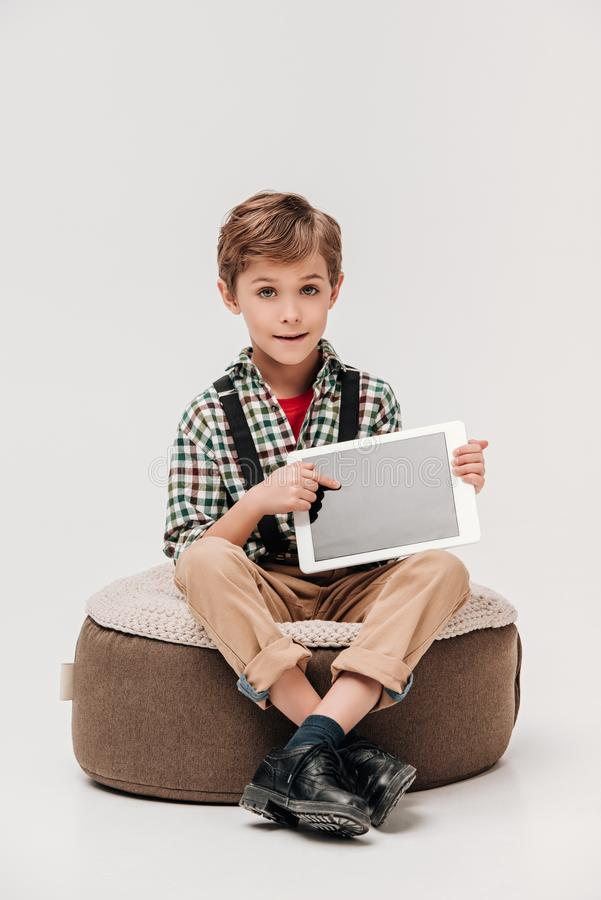 netter kleiner Junge, der digitale Tablette mit leerem Bildschirm zeigt und Kamera betrachtet stockbilder