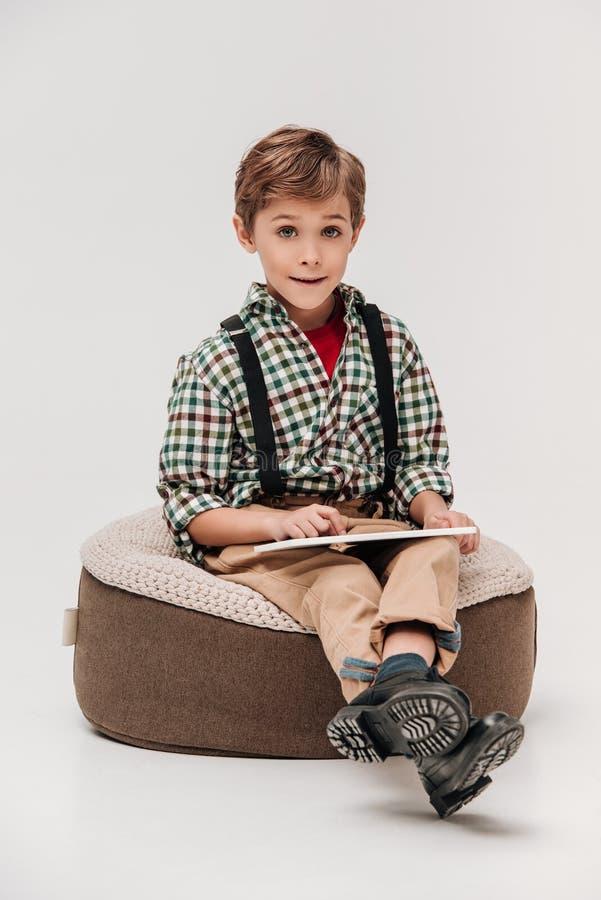 netter kleiner Junge, der digitale Tablette verwendet und an der Kamera lächelt lizenzfreie stockfotos