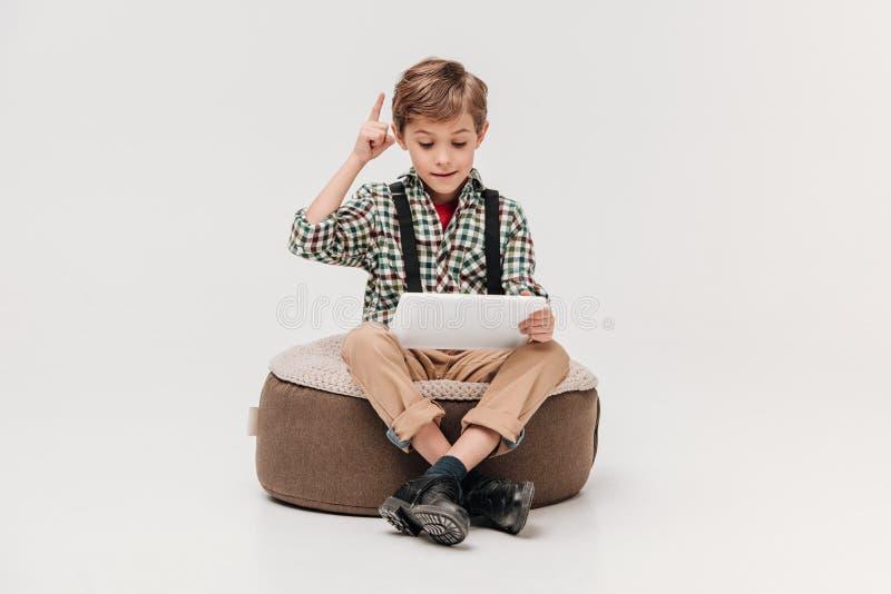 netter kleiner Junge, der digitale Tablette verwendet und oben mit dem Finger zeigt lizenzfreies stockfoto