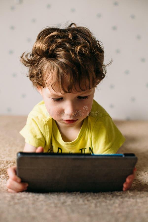 Netter kleiner Junge, der eine Auflage verwendet Kind, das mit der digitalen Tablette liegt auf einem Bett spielt Stillstehen - t stockfotografie