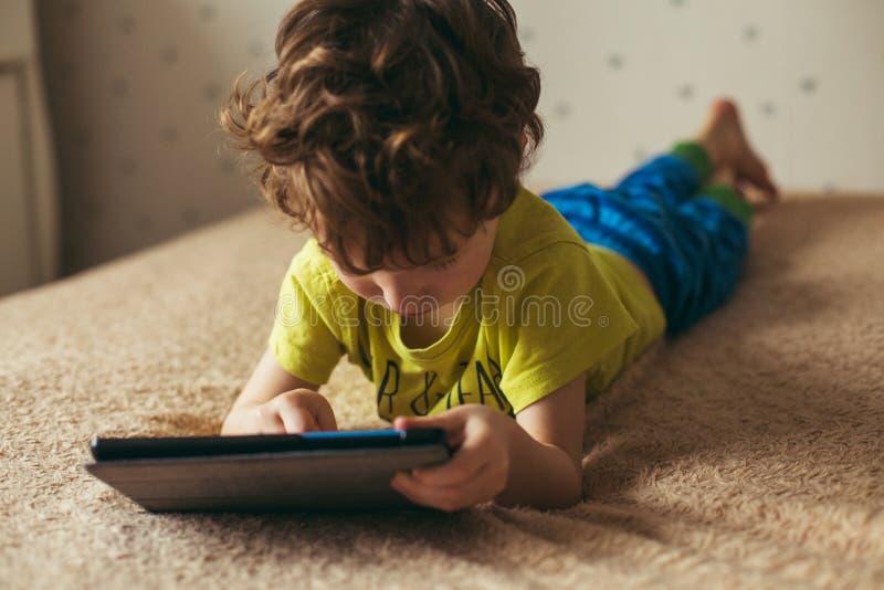 Netter kleiner Junge, der eine Auflage verwendet Kind, das mit der digitalen Tablette liegt auf einem Bett spielt Stillstehen - t lizenzfreie stockfotos