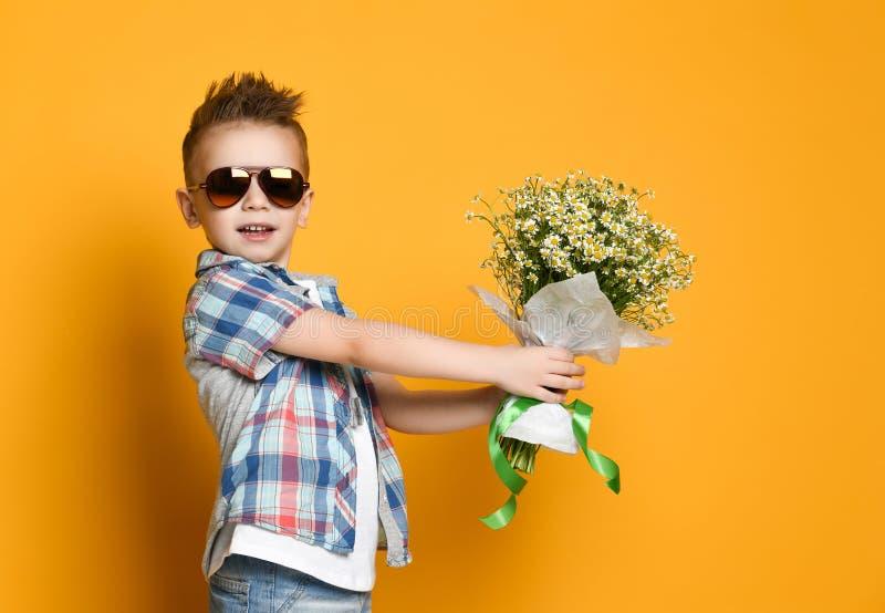 Netter kleiner Junge, der einen Blumenstrauß von Blumen hält lizenzfreie stockfotografie
