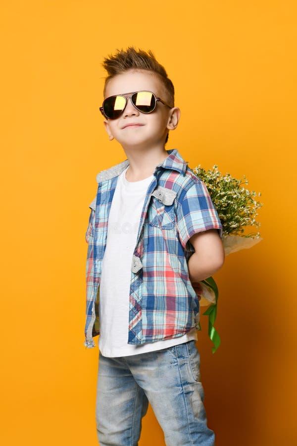 Netter kleiner Junge, der einen Blumenstrau? von Blumen h?lt lizenzfreie stockfotografie