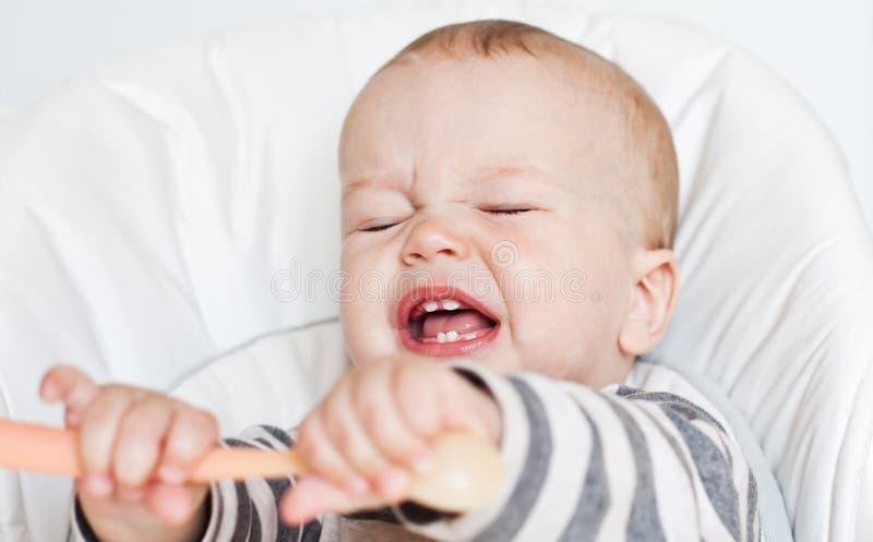 Netter kleiner Junge, der einen Löffel halten schreit stockbilder