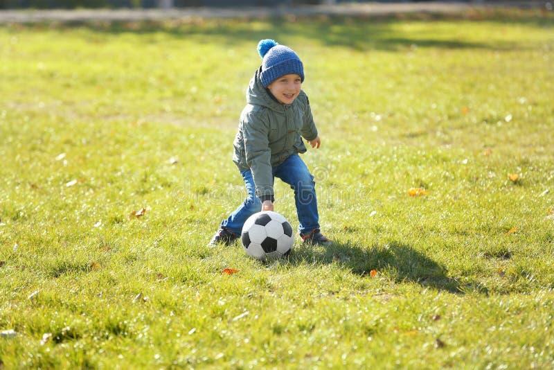 Netter kleiner Junge, der Fußball auf Neigung spielt lizenzfreie stockfotos