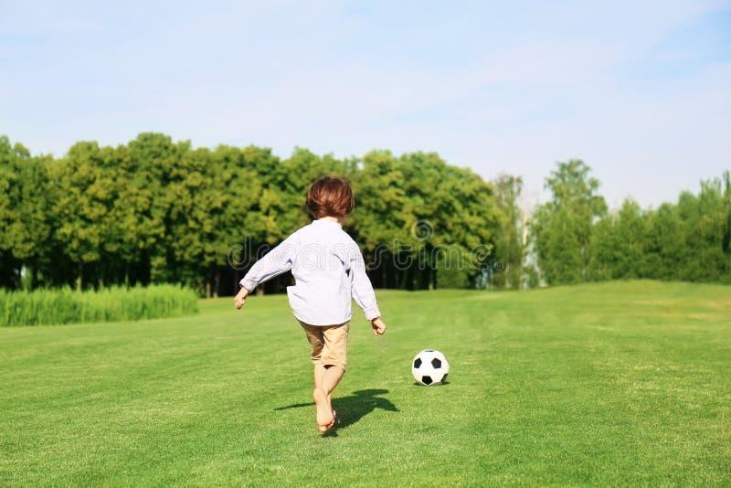 Netter kleiner Junge, der Fußball im Park am sonnigen Tag spielt lizenzfreies stockbild