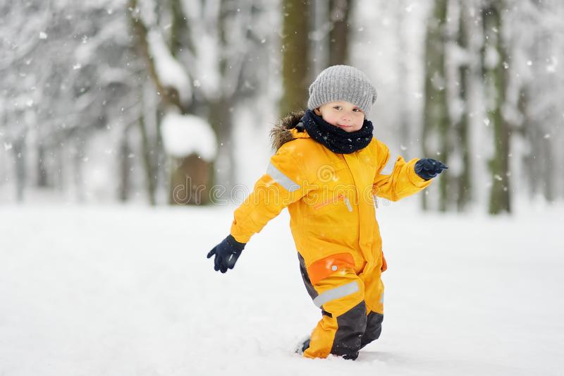 Netter kleiner Junge in der gelben Winterkleidung geht während Schneefälle stockbilder