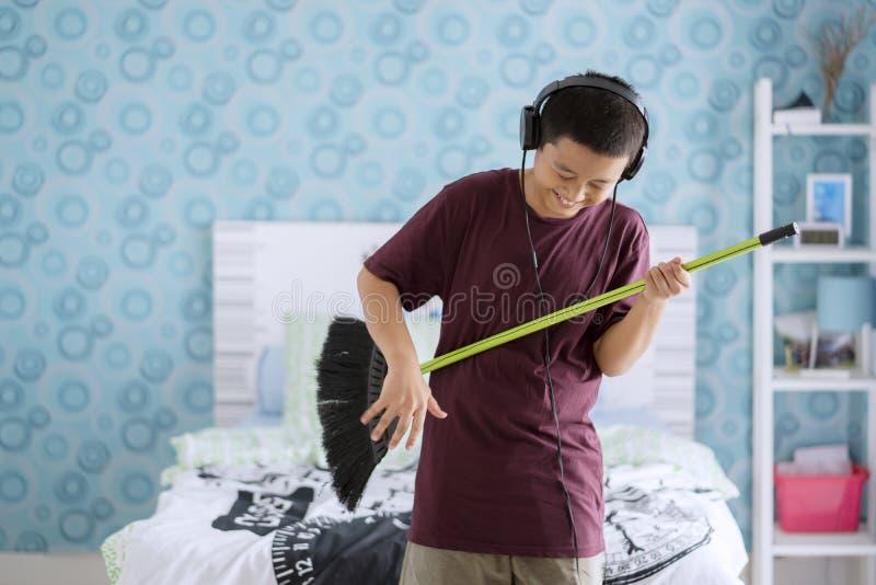 Netter kleiner Junge, der Gitarre durch die Anwendung eines Besens spielt stockfotos