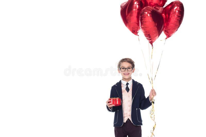 netter kleiner Junge in der Klage und die Brillen, die rotes Herz halten, formten Ballone und Geschenkbox stockbilder