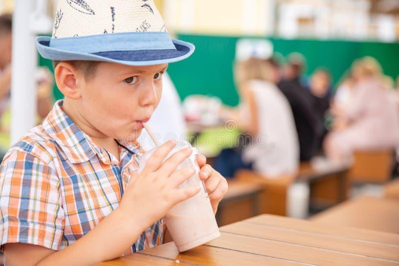Netter kleiner Junge, der Milchshake während der tropischen Ferien genießt stockbild