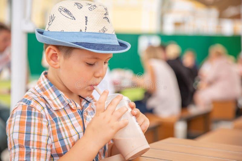 Netter kleiner Junge, der Milchshake während der tropischen Ferien genießt lizenzfreie stockfotografie