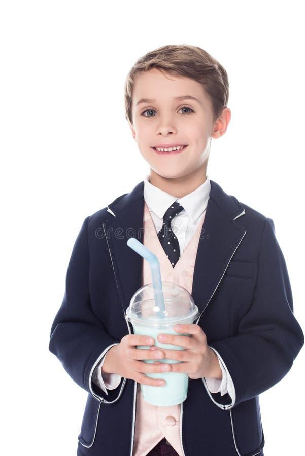 netter kleiner Junge, der Milchshaken in der Plastikschale hält und an der Kamera lächelt lizenzfreies stockbild