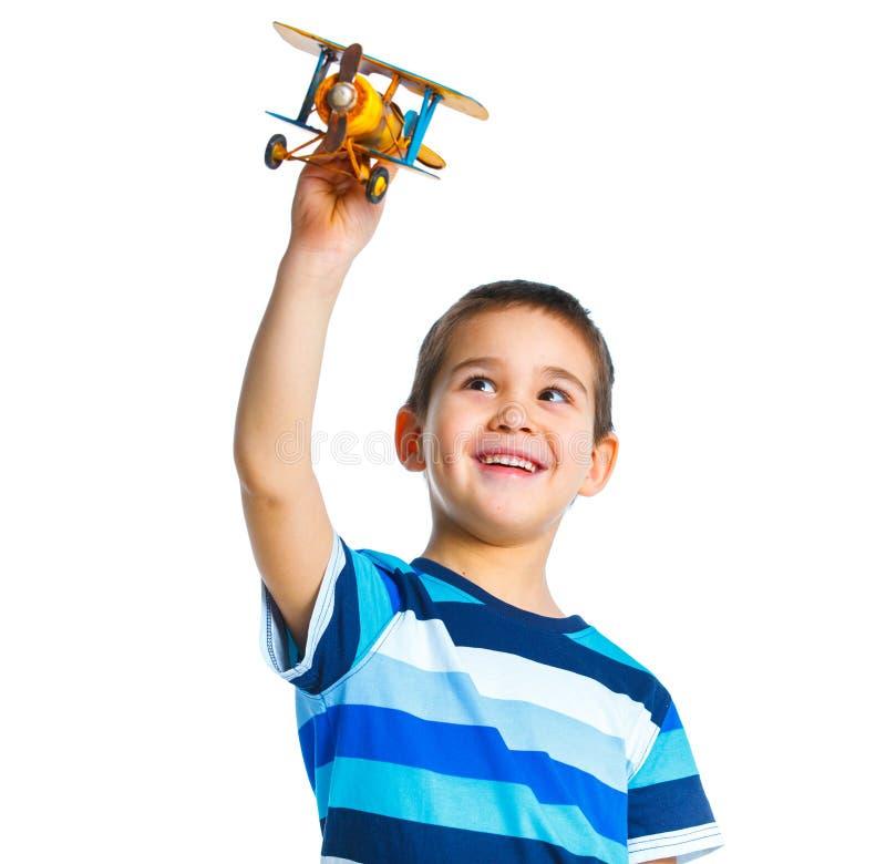 Netter kleiner Junge, der mit einem Spielzeugflugzeug spielt lizenzfreie stockfotos