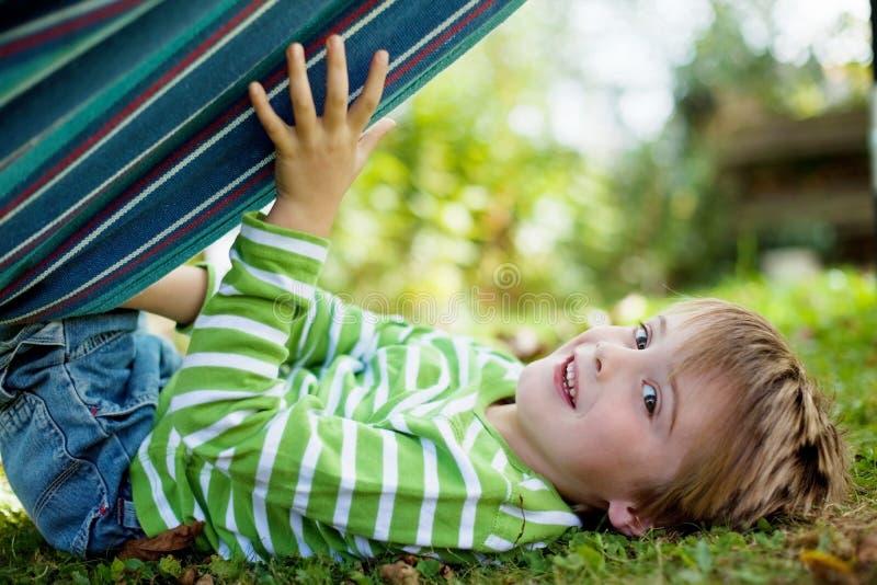 Netter kleiner Junge, der mit Hängematte spielt stockfotografie