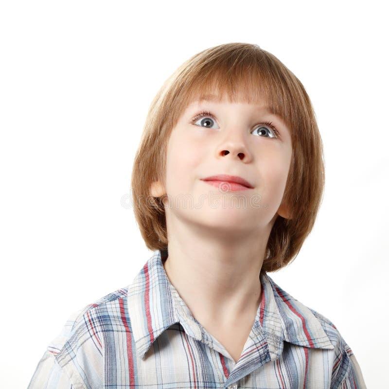 Netter kleiner Junge, der oben über Weiß schaut stockfoto