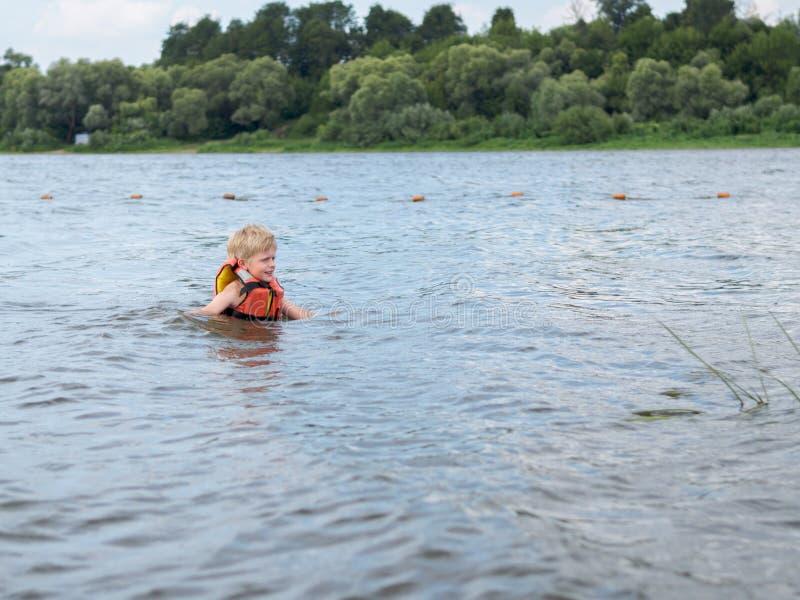 Netter kleiner Junge in der orange Schwimmwesteschwimmen im Fluss lizenzfreies stockfoto