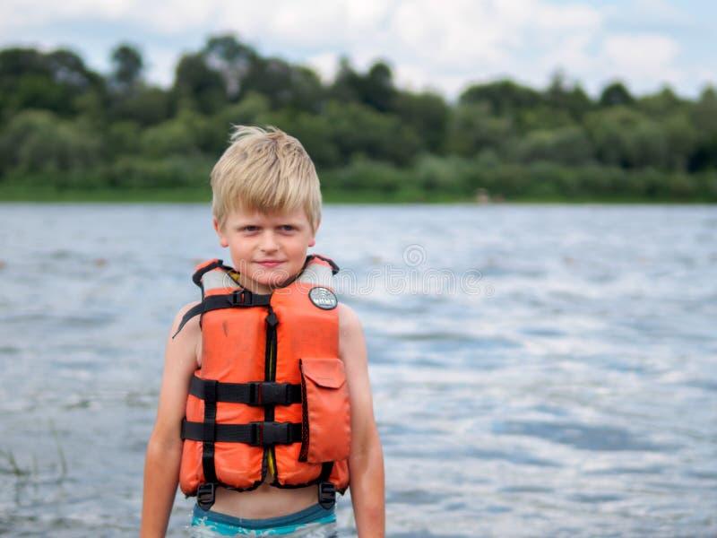 Netter kleiner Junge in der orange Schwimmwesteschwimmen im Fluss stockbilder