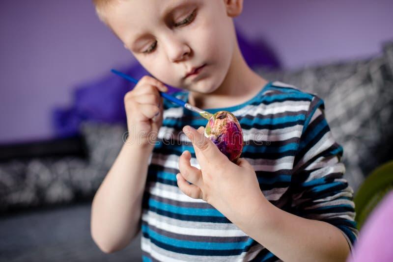 Netter kleiner Junge, der Osterei malt lizenzfreie stockbilder