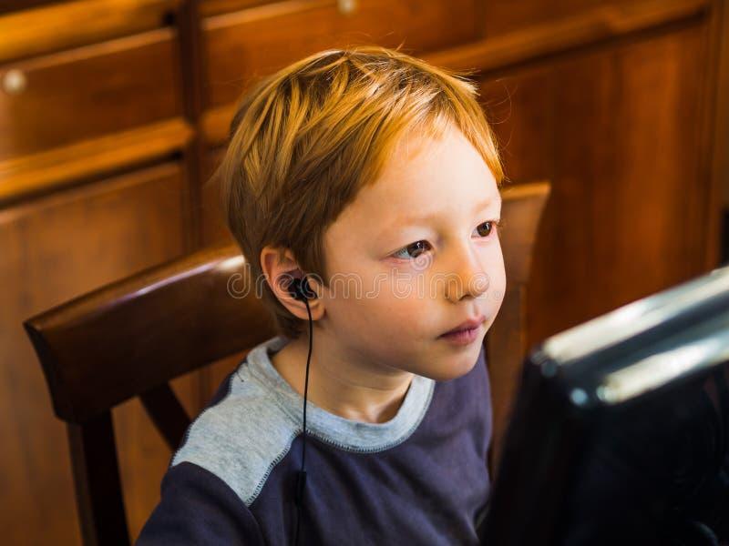 Netter kleiner Junge, der am PC konzentriert spielt lizenzfreie stockbilder