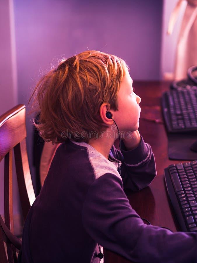 Netter kleiner Junge, der am PC konzentriert spielt lizenzfreies stockbild
