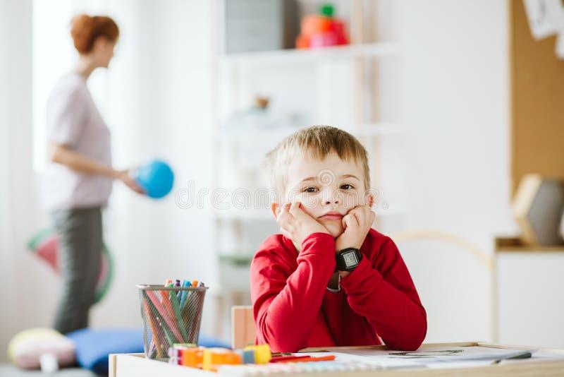 Netter kleiner Junge, der rotes Strickjackensitzen am kleinen Holztisch tr?gt lizenzfreie stockfotografie