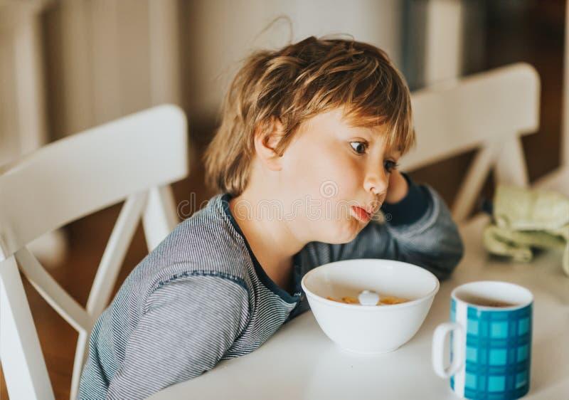 Netter kleiner Junge, der seine Getreide mit Milch isst lizenzfreie stockbilder