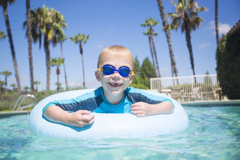 Netter kleiner Junge, der Spaß im Swimmingpool während im Urlaub hat stockbilder