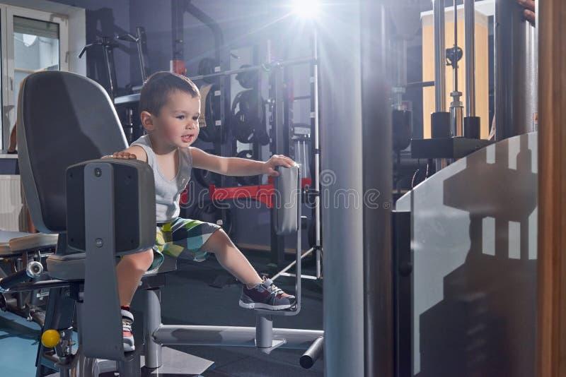 Netter kleiner Junge, der versucht, auf schwerem metallischem Simulator in der Turnhalle auszubilden lizenzfreie stockfotografie