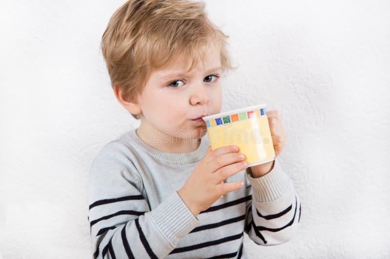 Netter kleiner Junge, der von einem Cup trinkt lizenzfreies stockbild