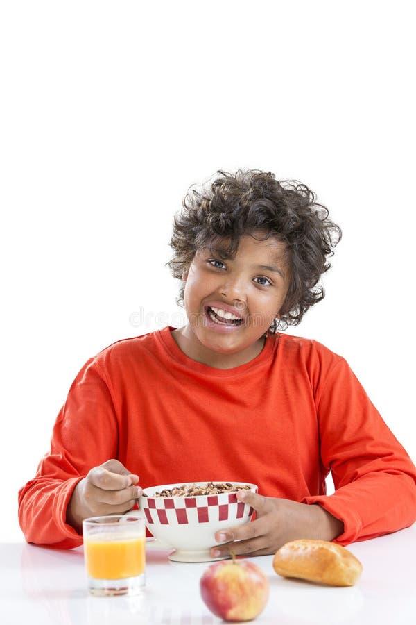 Netter kleiner Junge, der zu Hause eine große Schüssel Milch trinkend im roten T-Shirt frühstückt stockfotos