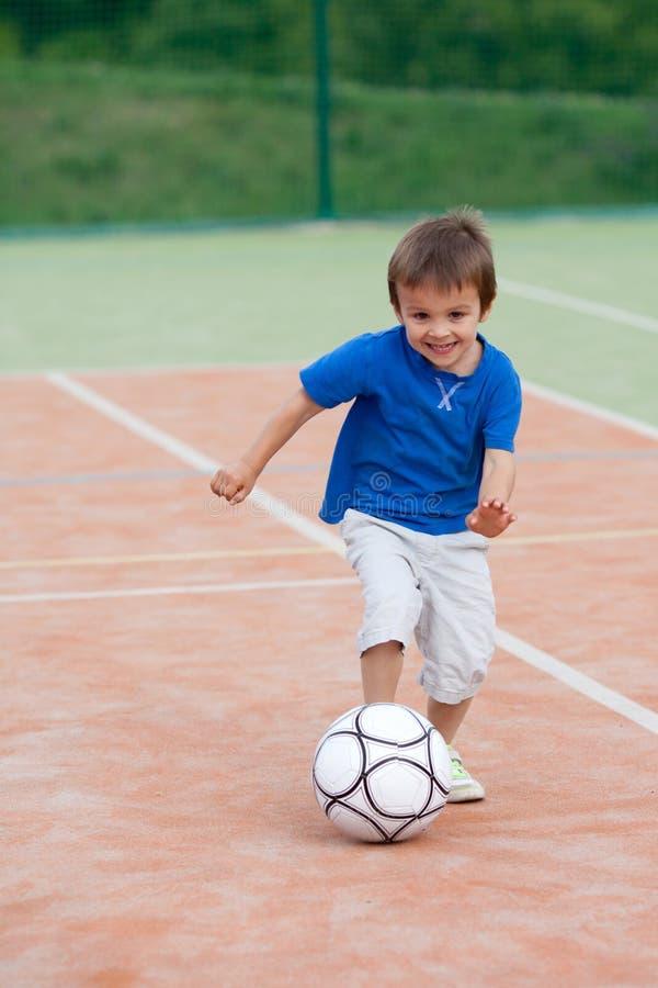 Netter kleiner Junge, Fußball spielend stockfotografie