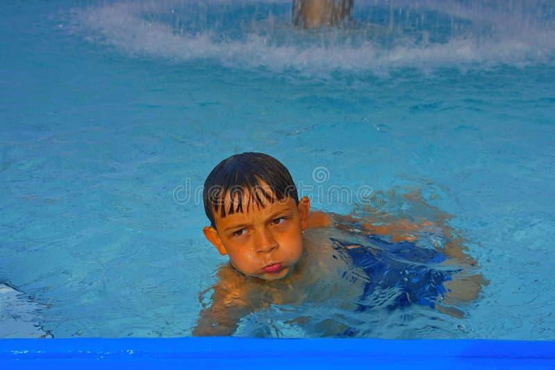 Netter kleiner Junge im Swimmingpool am Sommertag Sommer und glückliches Kindheitskonzept Kopieren Sie Raum im hellen blauen Wass stockfotografie