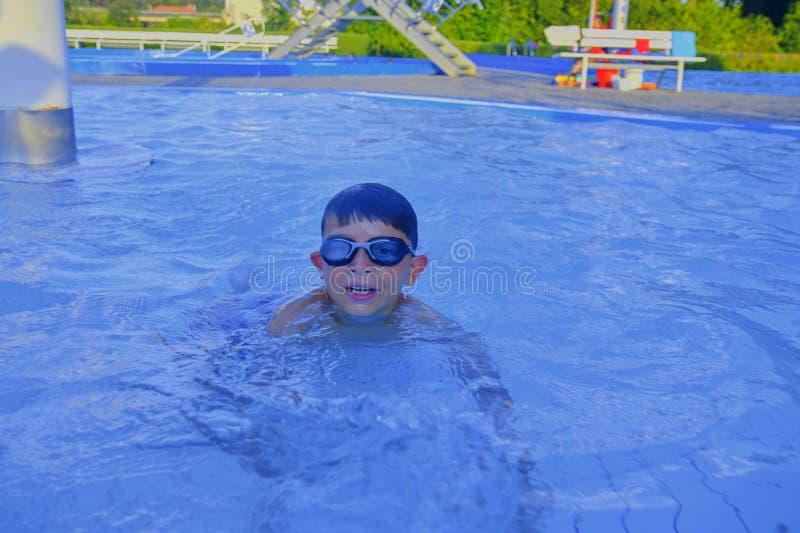 Netter kleiner Junge im Swimmingpool am Sommertag Sommer und glückliches Kindheitskonzept Kopieren Sie Raum im hellen blauen Wass lizenzfreies stockfoto