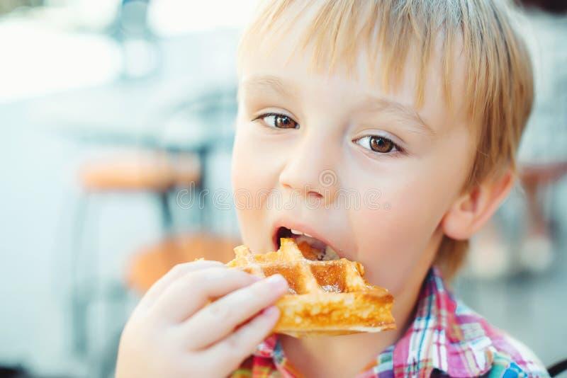 Netter kleiner Junge isst geschmackvolle belgische Waffel auf Sommerterrasse lizenzfreies stockbild