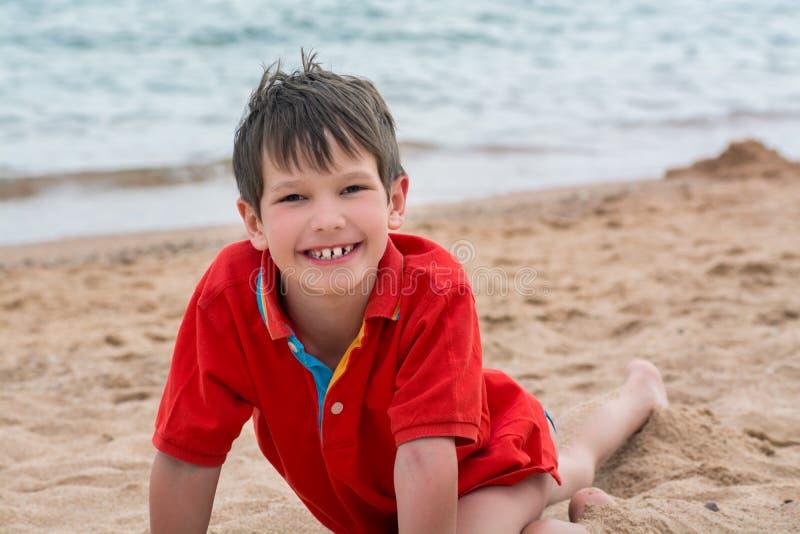 Netter kleiner Junge liegt auf dem Sand auf der glücklichen Küste, lizenzfreies stockbild