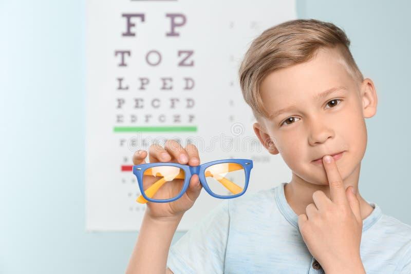 Netter kleiner Junge mit Brillen im Büro stockbild