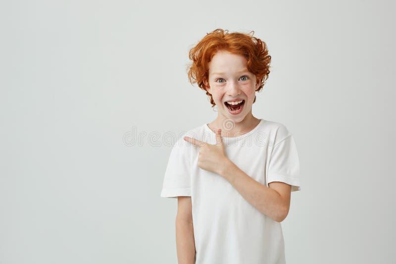 Netter netter kleiner Junge mit dem gelockten Ingwerhaar und den Sommersprossen glückliches mit dem Finger auf Weiß beiseite läch lizenzfreies stockbild