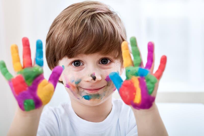 Netter kleiner Junge mit den farbigen Händen lizenzfreies stockfoto