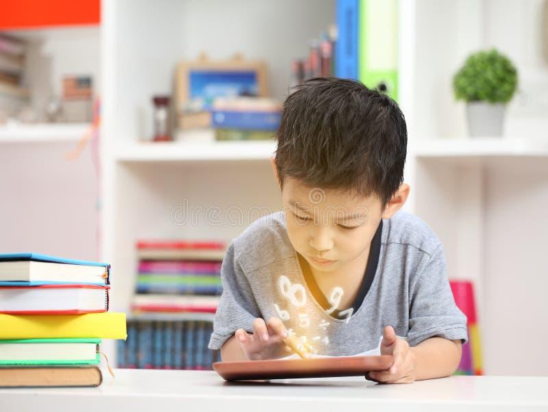 Netter kleiner Junge mit der digitalen Tablette, früh lernend asiatischer Junge pl lizenzfreie stockbilder