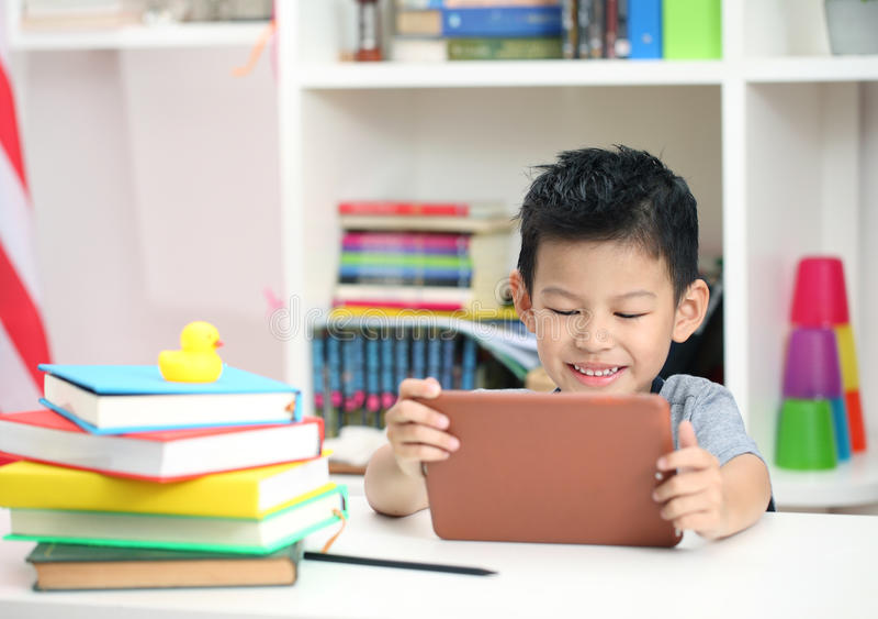 Netter kleiner Junge mit der digitalen Tablette, früh lernend asiatischer Junge pl lizenzfreie stockfotos