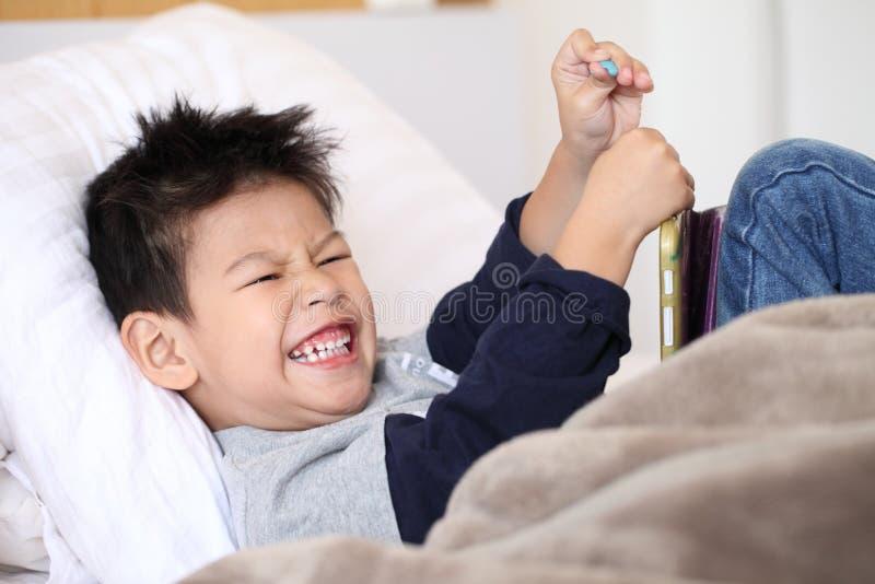 Netter kleiner Junge mit der digitalen Tablette, früh lernend asiatischer Junge, der Spiel auf dem Schlafzimmer spielt lizenzfreie stockbilder