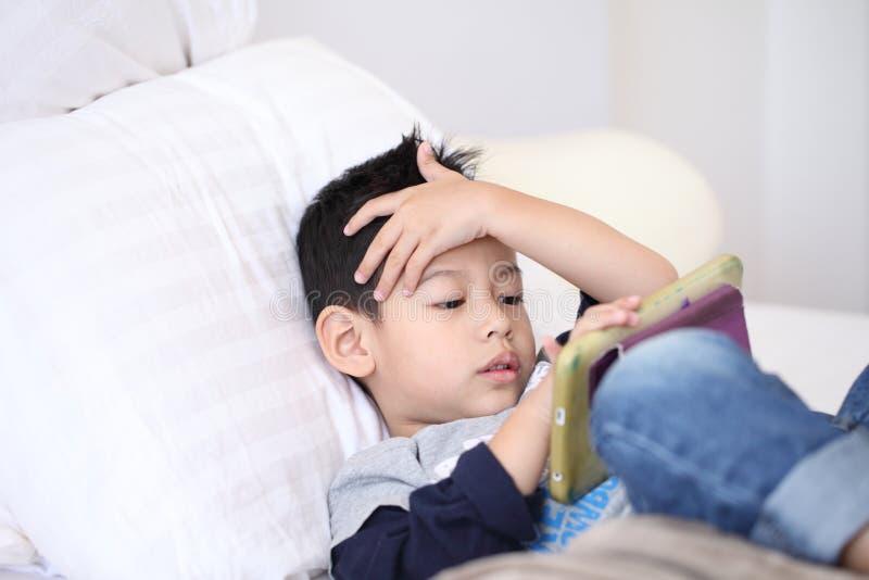 Netter kleiner Junge mit der digitalen Tablette, früh lernend asiatischer Junge, der Spiel auf dem Schlafzimmer spielt stockbilder
