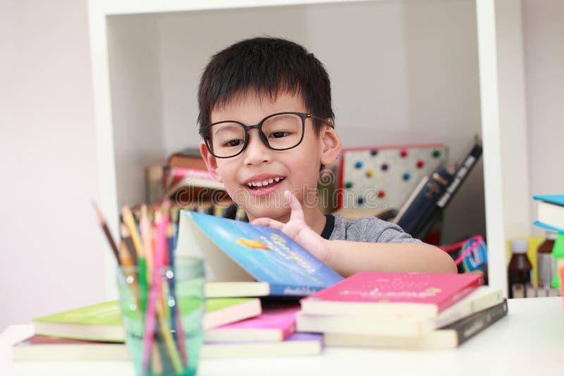 Netter kleiner Junge mit der digitalen Tablette, früh lernend asiatischer Junge, der Spiel auf dem Schlafzimmer spielt stockfotografie
