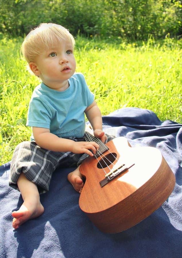 Netter kleiner Junge mit der hawaiischen Gitarre der Ukulele im Freien Baby, das Musikinstrument erforscht stockfotografie