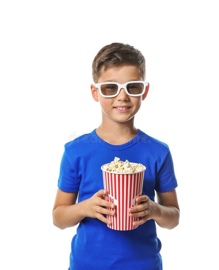 Netter kleiner Junge mit der Schale Popcorn des Kinos 3D auf weißem Hintergrund tragend Gläser stockbilder