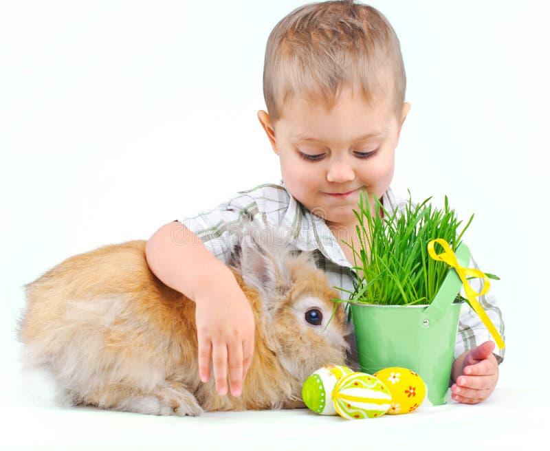 Netter kleiner Junge mit Häschen- und Ostereiern stockfoto