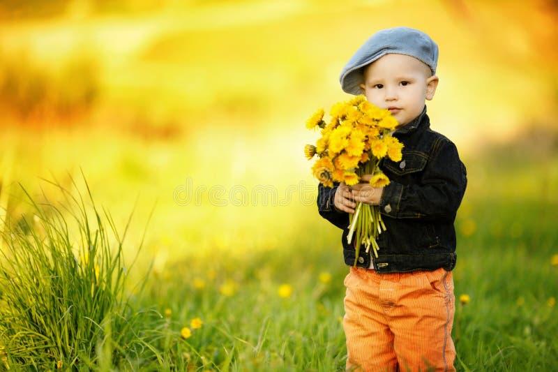 Netter kleiner Junge mit Löwenzahn stockfotografie