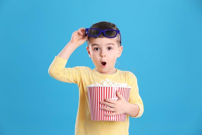 Netter kleiner Junge mit Popcorn und Gläsern stockfoto